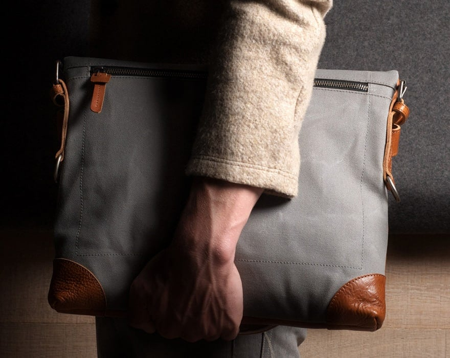 Image of a man's arm clutching a gray bag with leather trim | Toronto Employment Lawyers | notice and Severance