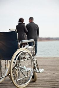 A couple in the background standing in front of a lake with a wheelchair in the foreground | Disability Claim Denied | Disability Benefits Cut Off
