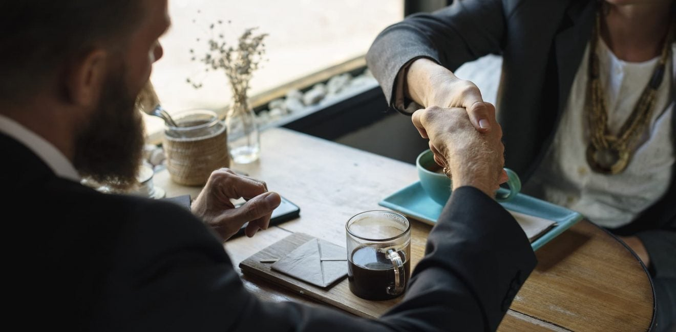 Man & Woman shaking hands over a coffee   Commission Sales Agents