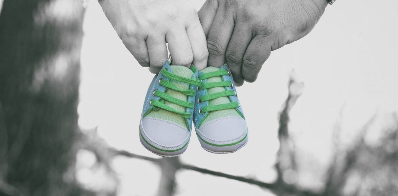 Parent Employee Rights | Parental Leave | Close up of a couple's hands carrying a pair of baby shoes