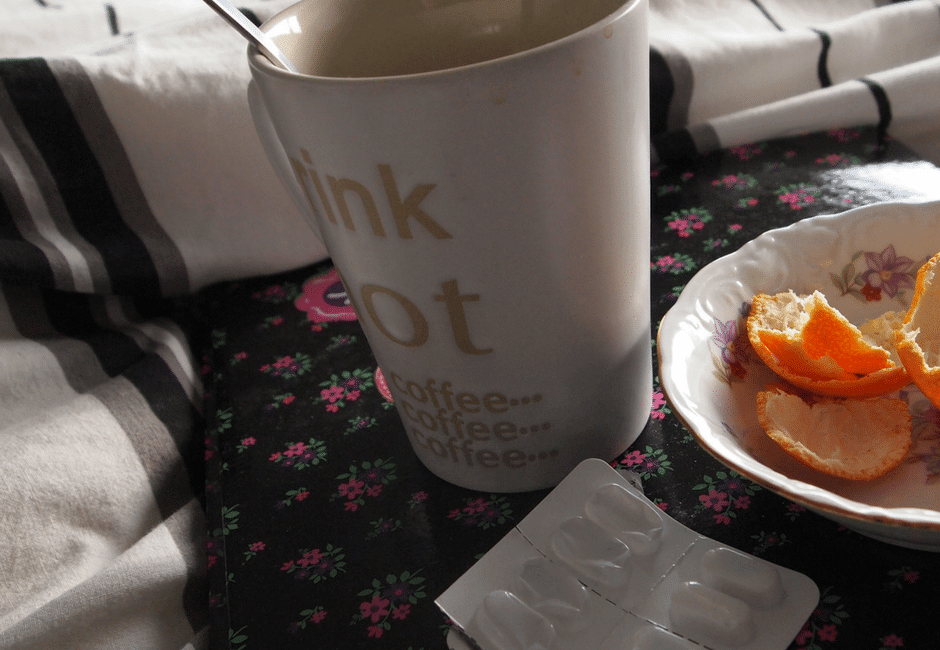 Sick leave | coffee cup, orange peels in a plate next to medicine on a bed
