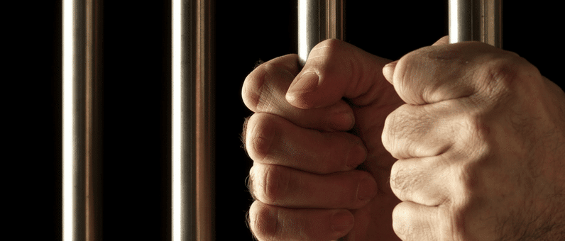 Criminal Records | close up of male hands holding jail bars