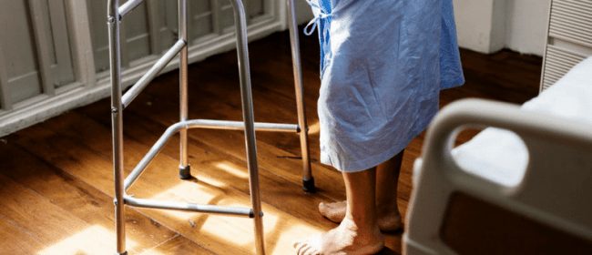 Fired While Ill | man in a hospital gown trying to walk with a walker