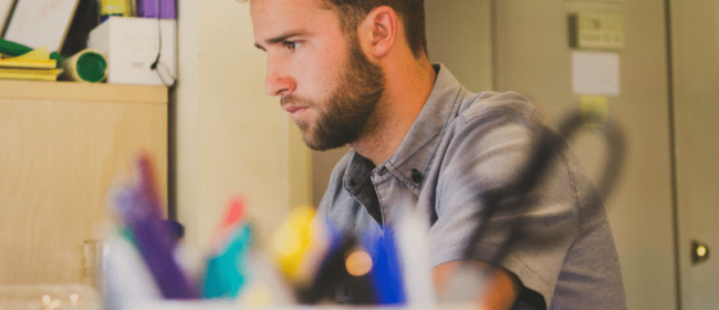 Young man looking pensive at a computer screen | misclassifying Contract Workers