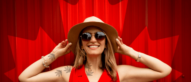 workplace law for Cannabis Users | Woman with cannabis leaf tattoos smiling in front of a curtain with the Canadian Maple Leaf